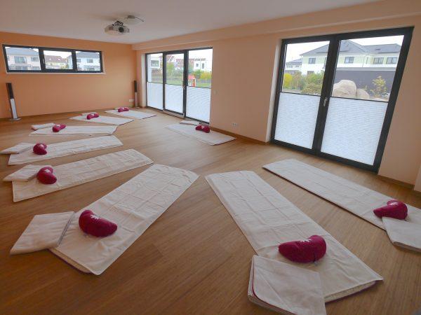 Innenaufnahme Yogaraum Human Unfoldment Leipzig. Mit Yogamatten, Yogatüchern, Meditationskissen und Wolldecken. Der Blick durch die große Fensterfront fällt in den Garten.