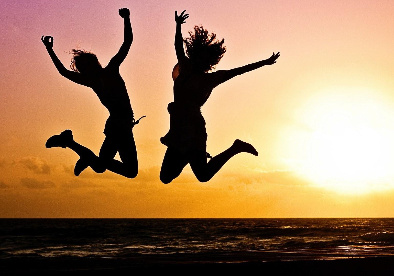 Selbsterfahrung heißt frei werden von den Prägungen unserer Vergangenheit. Symbolisiert durch Sprung von Mann und Frau vor der Abendsonne.