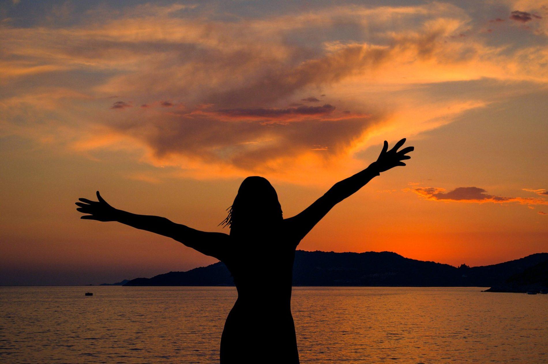 Yoga als Weg der Selbsterfahrung. Frau atmet durch vor dem Abendrot.